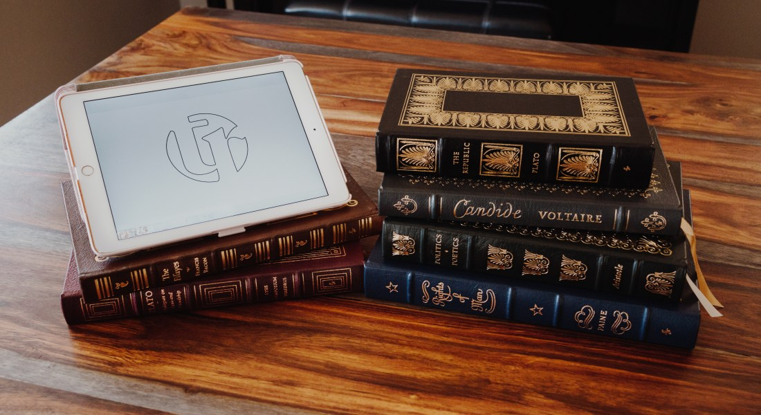 A stack of gilded leather philosophical books sits next to an iPad displaying the Tabula Rasa logo.