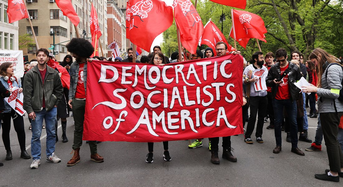 "A group of protesters holds a banner that reads ""Democratic Socialists of America."""