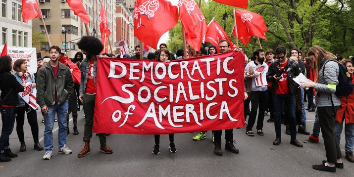 """A group of protesters holds a banner that reads """"Democratic Socialists of America."""""""