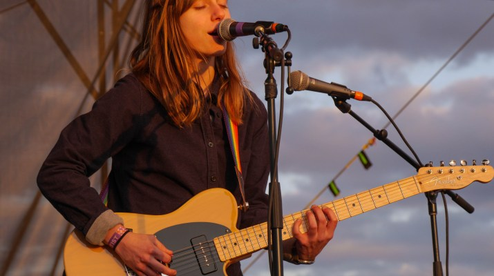 A person with long brown hair holds a yellow guitar and sings into a microphone with their eyes closed.