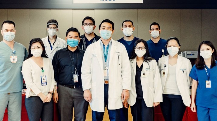 Eleven people wearing surgical masks and coats look at the camera.