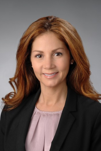 A woman has red hair and wears a lavender top and black blazer.