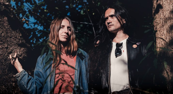 Two people with long hair are posing by a tree