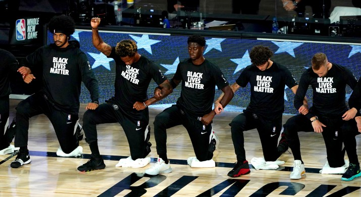 """NBA basketball players wearing """"Black Lives Matter"""" shirts kneel on the court and raise their fists."""