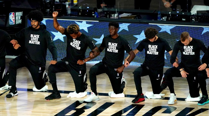 "NBA basketball players wearing ""Black Lives Matter"" shirts kneel on the court and raise their fists."