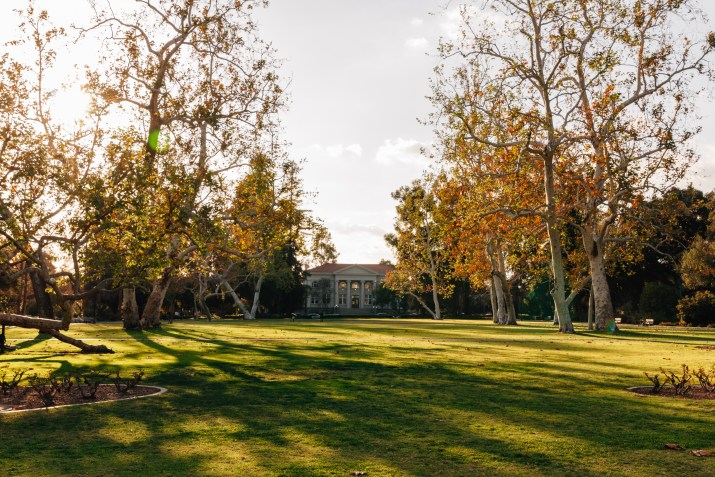 A white building sits at the end of a green quad lined with trees.