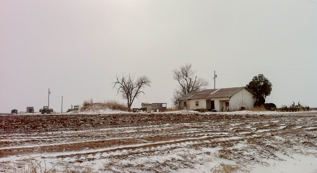 A white farmhouse sits on a brown field covered in snow.