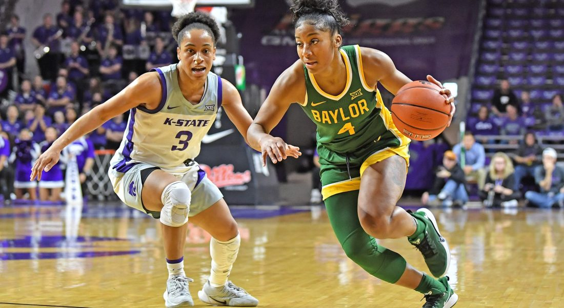 Two female NCAA basketball players contend for the ball during a game.