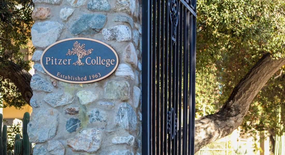 """A stone pillar next to a black iron gate has a metal sign saying """"Pitzer College."""""""