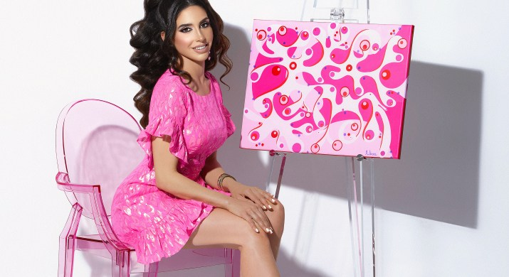 A woman with long, brown hair wears a pink dress while sitting on a pink chair in front of a pink painting.