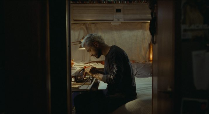 A man with blonde hair sits in a room working on a project at a desk.