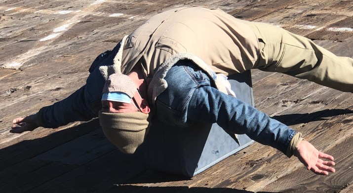 A person wearing a blue, denim jacket, yellow pants, and a beige hat lays on a blue box with their arms and legs spread out to each side.