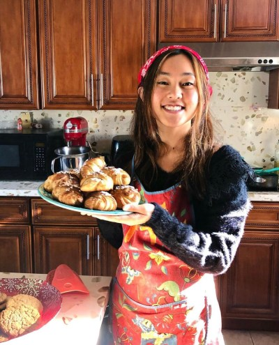 A woman wearing a black fuzzy sweater, red, flowerly apron and red bandana holds a plate of croissants.