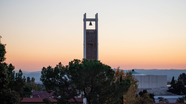 A white clocktower emerges from the trees and towers over other buildings in front of an orange and red sunset.