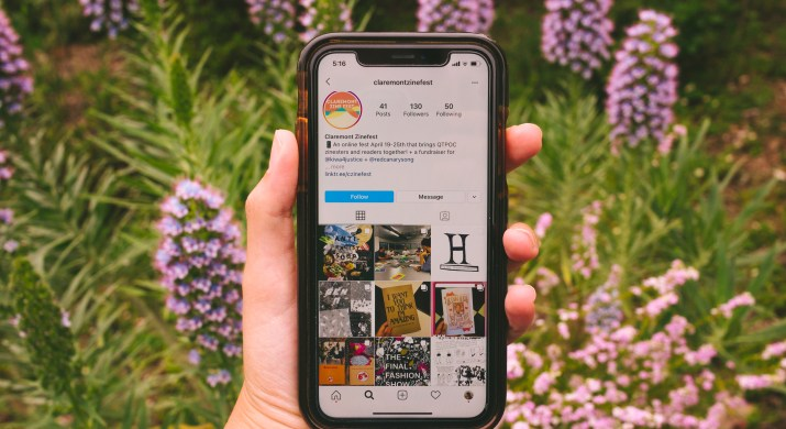 A hand holds a phone displaying the colorful Claremont Zinefest Instagram page in front of purple flowers.
