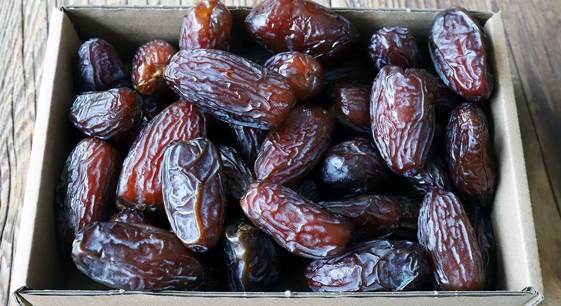 Many small dates sit in a cardboard box.