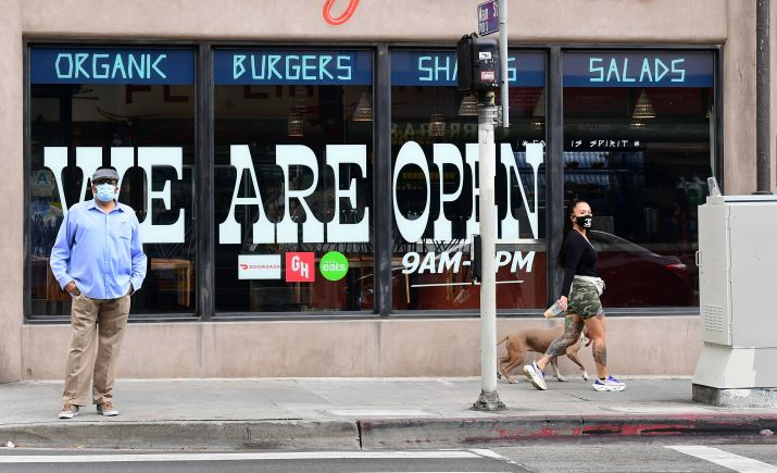"""A restaurant has a """"WE ARE OPEN"""" sign in its windows."""