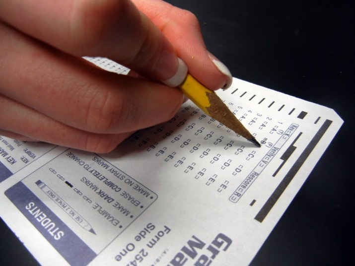 A person uses a yellow pencil to fill in a standardized testing sheet.