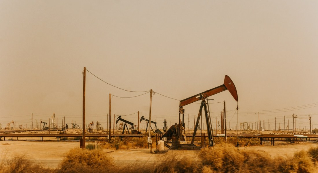 Many metal oil drills stand on a flat, yellow field.