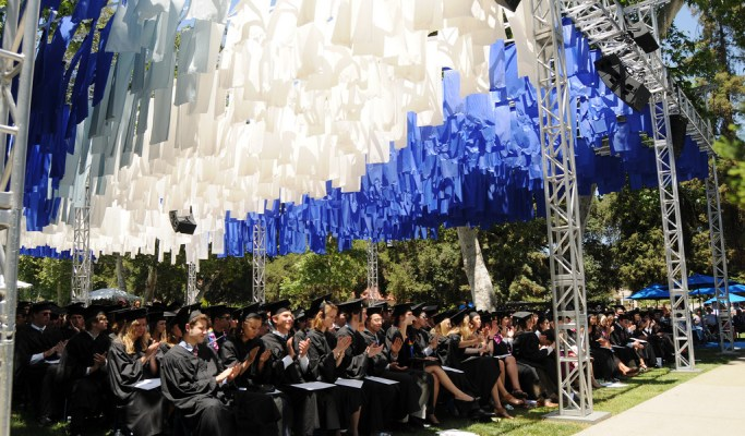 People wearing black caps and gown sit under blue and white streamers.