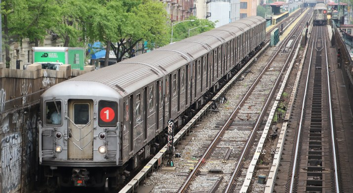 A silver, metal subway train sits on railroad tracks surrounded by trees and colorful apartment buildings.