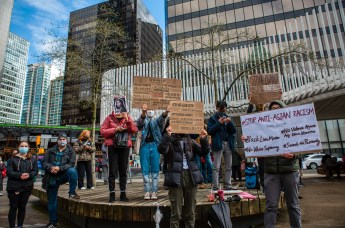 A Stop Asian Hate rally takes place in Vancouver in early 2021. Protestors stand on a stage holding signs that read: #STOP ANTI-ASIAN RACISM and STAND AGAINST RACISM