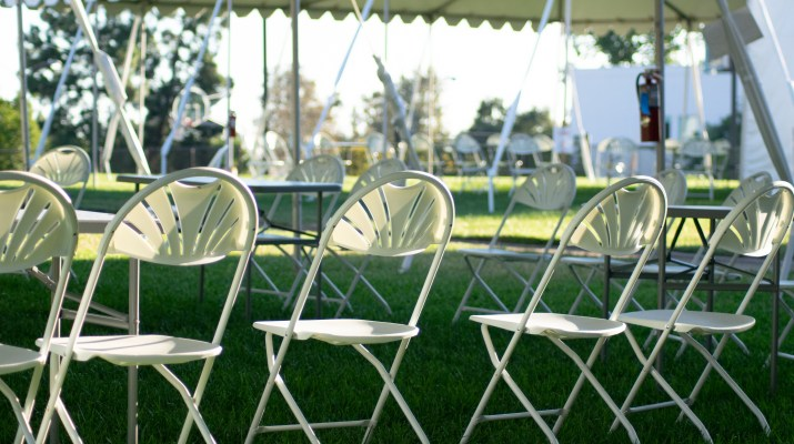 White chairs sit on a grassy field underneath a white tent.