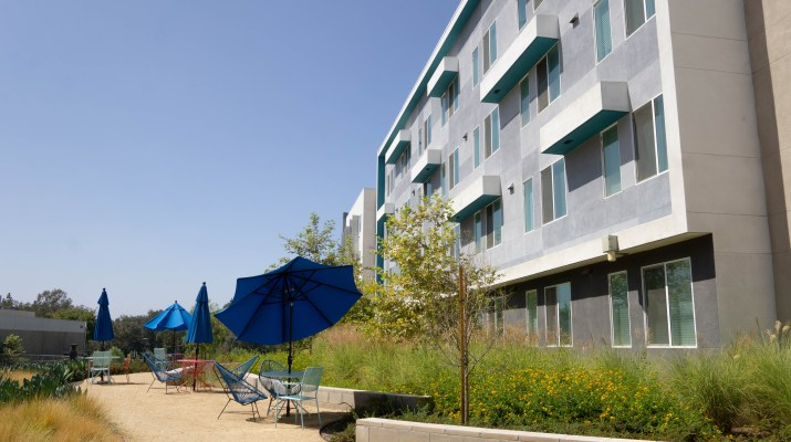 The exterior of the Oasis Apartments under clear skies.