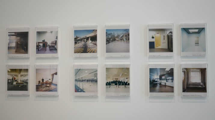Framed photos of different perspectives of a bowling alley hang on the wall.