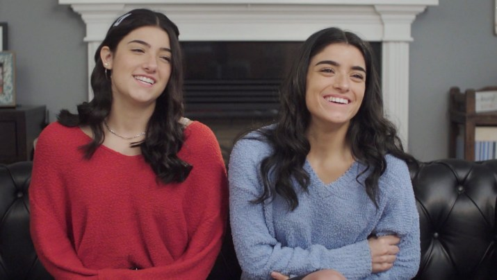 Two young women in sweaters laugh.