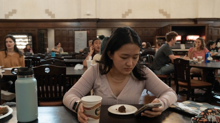 A student looks into her phone at a dining hall with a sad expression.