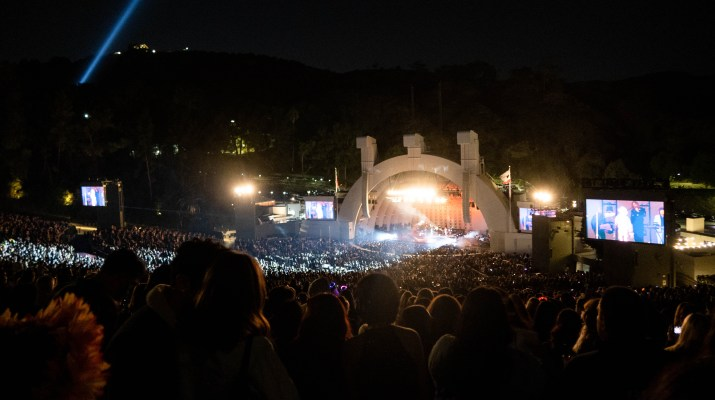 A huge crowd in an amphitheater have their attention on a huge stage on which a band plays.