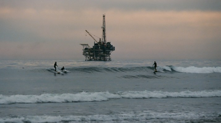 Three silhouettes of surfers surfing with an oil rig in the middle distance.