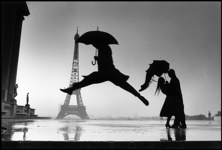 Photograph of figures near Eiffel Tower in the rain by Henri Cartier-Bresson