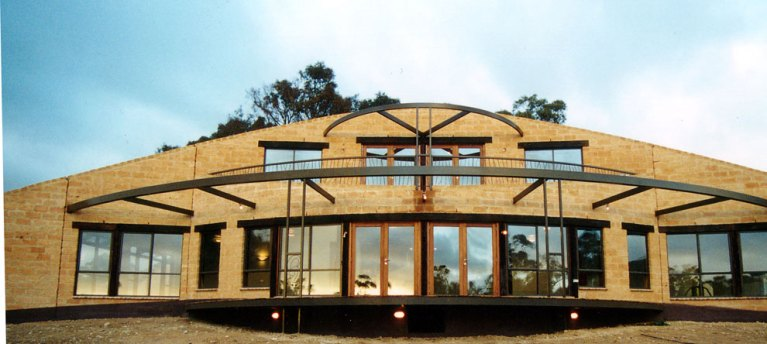 Autonomous Mud Brick House - curved mud brick walls and cantilevered deck - steel Shade structures