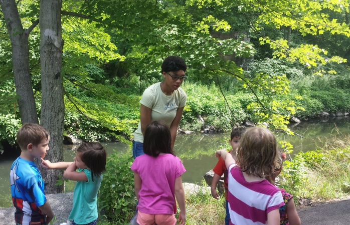 A group of children and one adult gather near Tacony Creek in Tacony Creek Park.