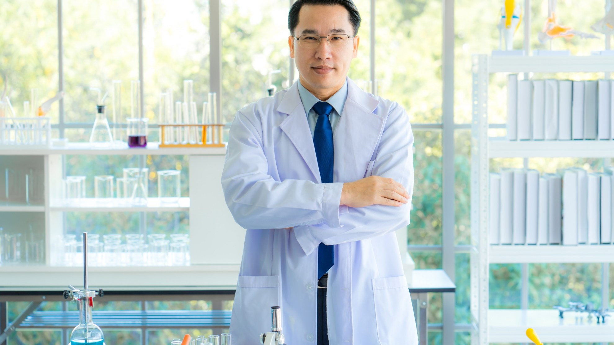 A middle aged man scientist smiling happily with his arms crossed posing at her laboratory colleagues. A confident professor CEO standing preparing equipment for teaching collage student. Copy space.