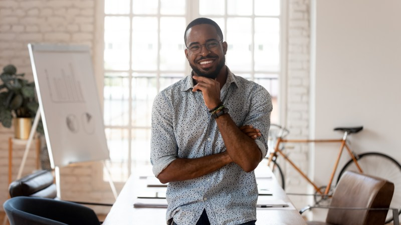 Happy african american businessman entrepreneur startup owner stand in modern office looking at camera, smiling young black designer creative occupation person posing in work space, business portrait