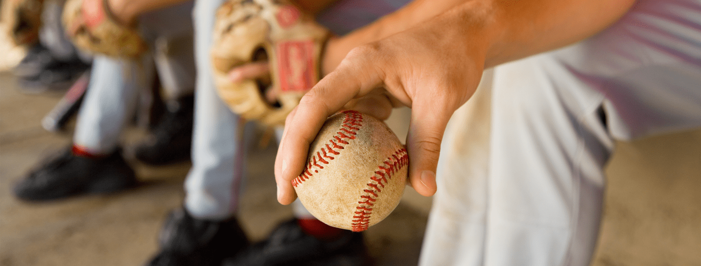 Baseball player in a dugout holding a baseball barehanded.