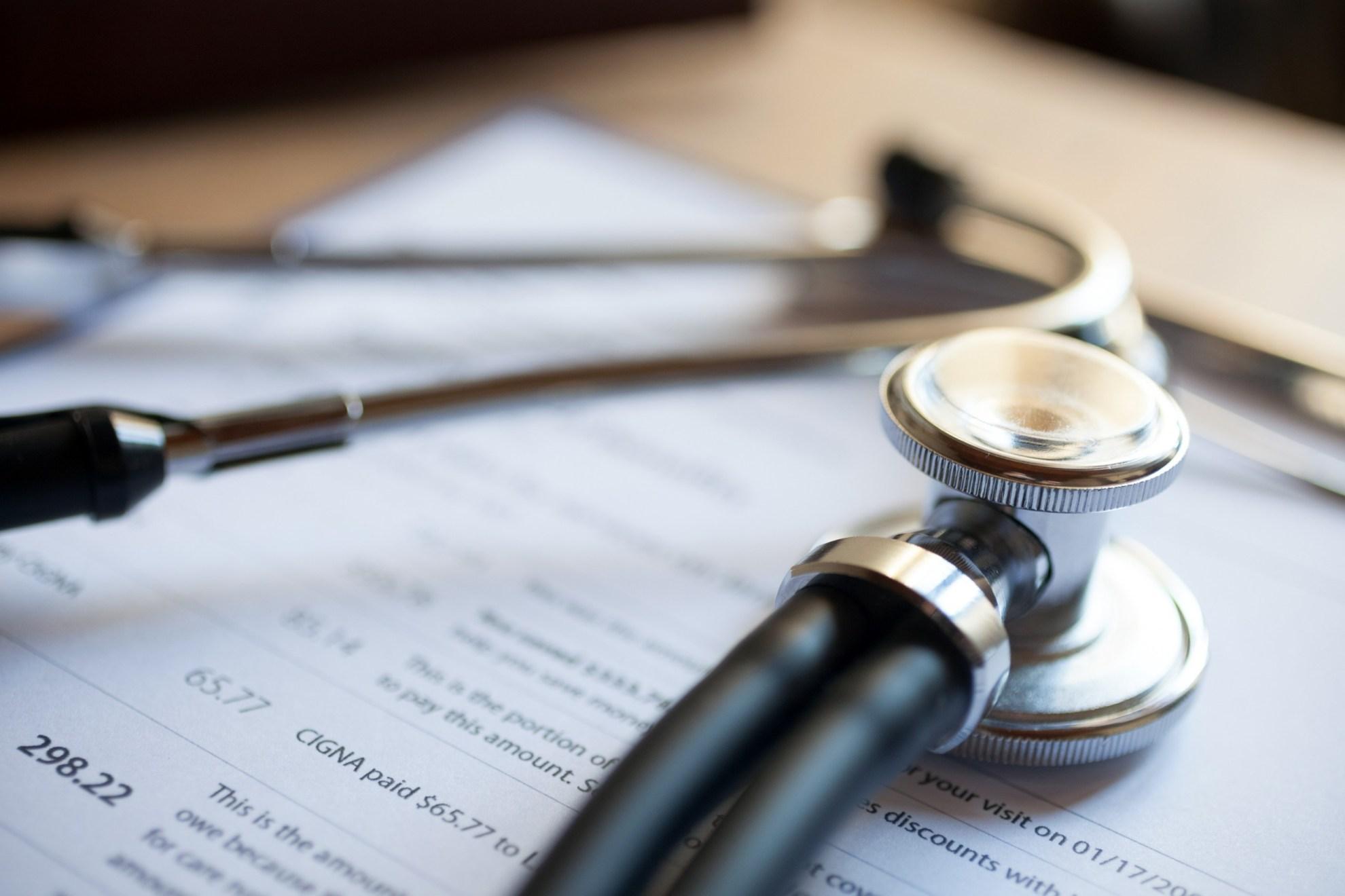 Insurance reimbursement paperwork on a clipboard under a stethoscope.