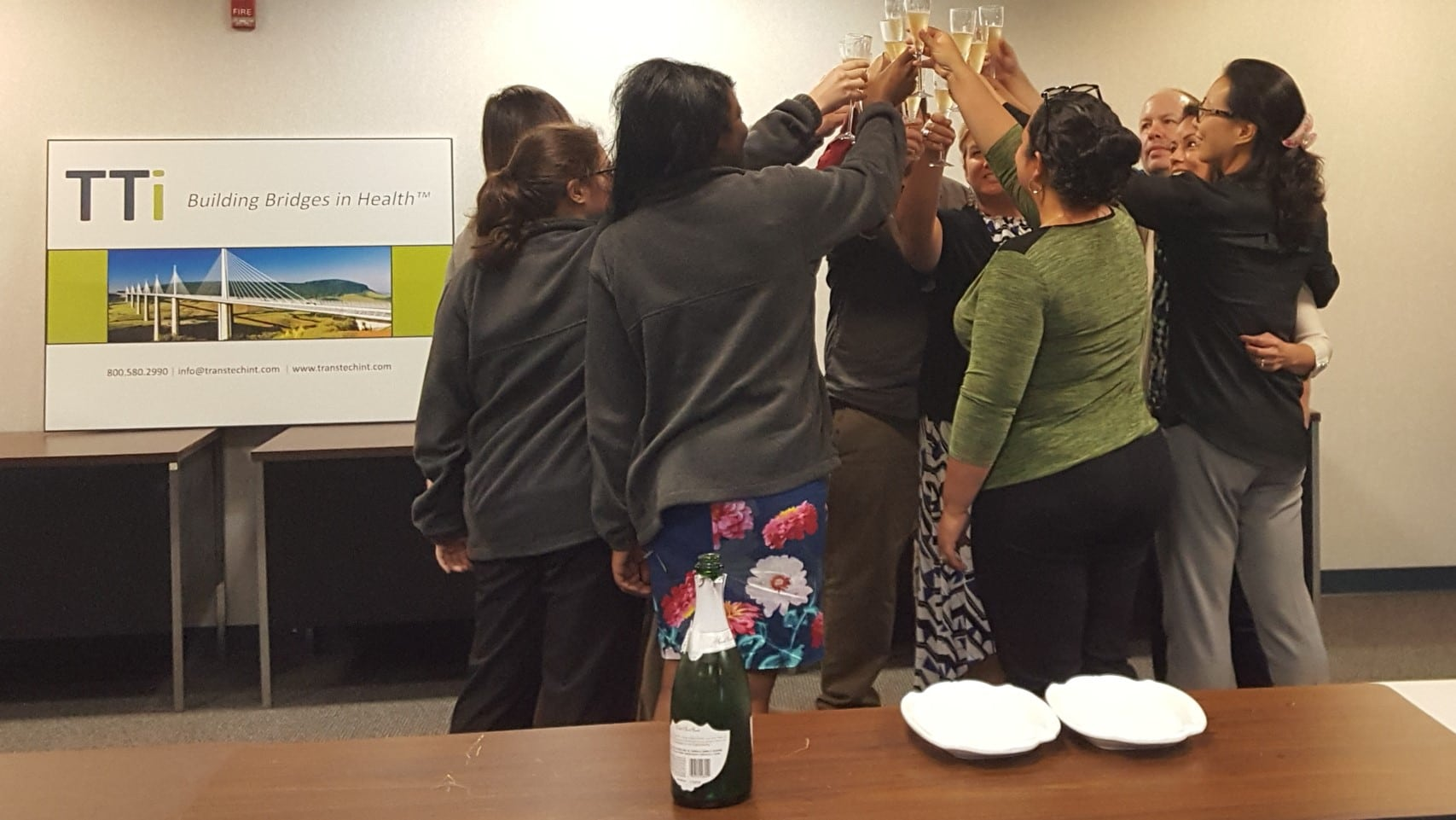 TTi employees in the conference room toasting with champagne in new office