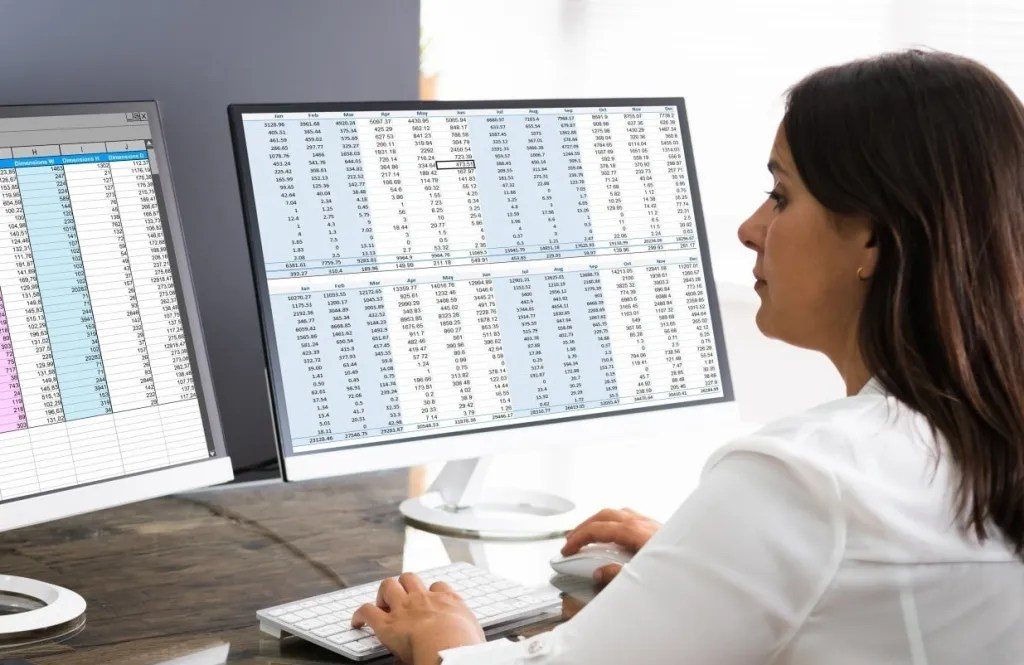 Analyst conducting due diligence and studying data in front of two computer monitors.