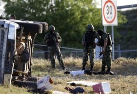 Soldiers stand over the body of a suspected hit man lying next to his overturned vehicle after a shootout in the municipality of China on the outskirts of Monterrey, Mexico, Tuesday, March 30, 2010. According to the army, two suspected hit men were killed during a shootout with soldiers along the highway to Reynosa after refusing to stop at a military checkpoint. (AP Photo/Claudio Cruz)