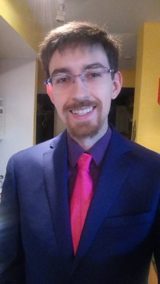 Austin Ramsay, a white man with glasses, and a well-trimmed beard, smiles confidently into the camera, wearing a blue suit, purple shirt and dashing pink tie