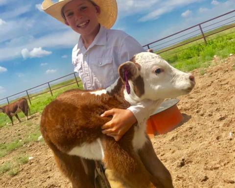 Photo of Ryder Day holding Cupid as a calf.