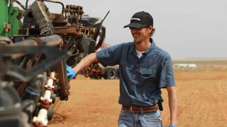 Picture of farmer inspecting equipment.