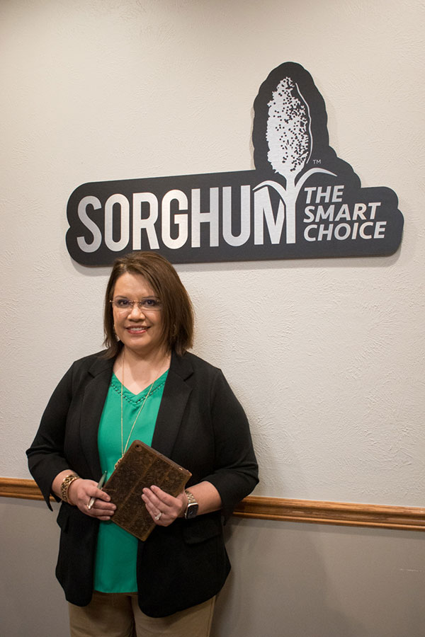 Picture of Norma Ritz Johnson next to the Sorghum sign.