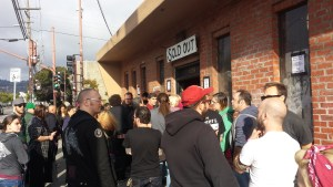 A crowd forms at the entrance of 924 Gilman Street.