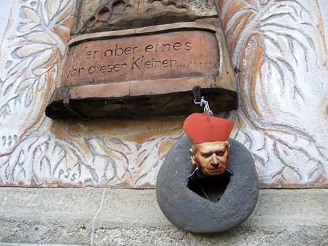 """Ein Foto Herman Groers mit einem Mühlstein hängt an einem Denkmal für """"Lebensschutz"""" an der Kirche in Hohenzell, OÖ"""