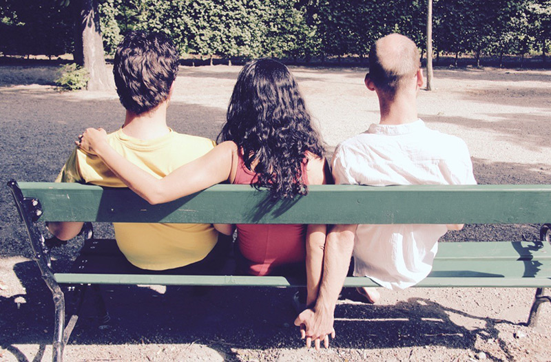 Eine Frau sitzt mit zwei Männern auf einer Bank